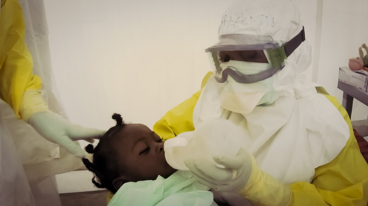 MSF national staff at an Ebola center in Sierra Leone tries to comfort a 10-month-old patient with Ebola as a fever takes hold. © Fabio Basone/MSF
