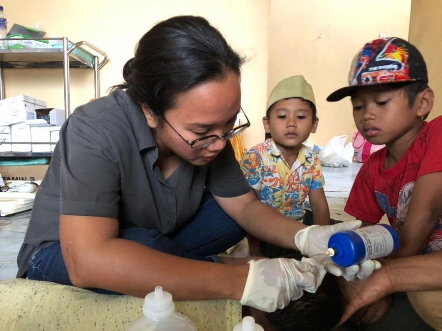 Le Dr Rangi Wirantika panse la plaie d'Adam, 4 ans, blessé lors du tremblement de terre qui a touché Palu le 28 Septembre 2018. Sulawesi central, Octobre 2018, © Sri Harjanti Wahyuningsih/MSF