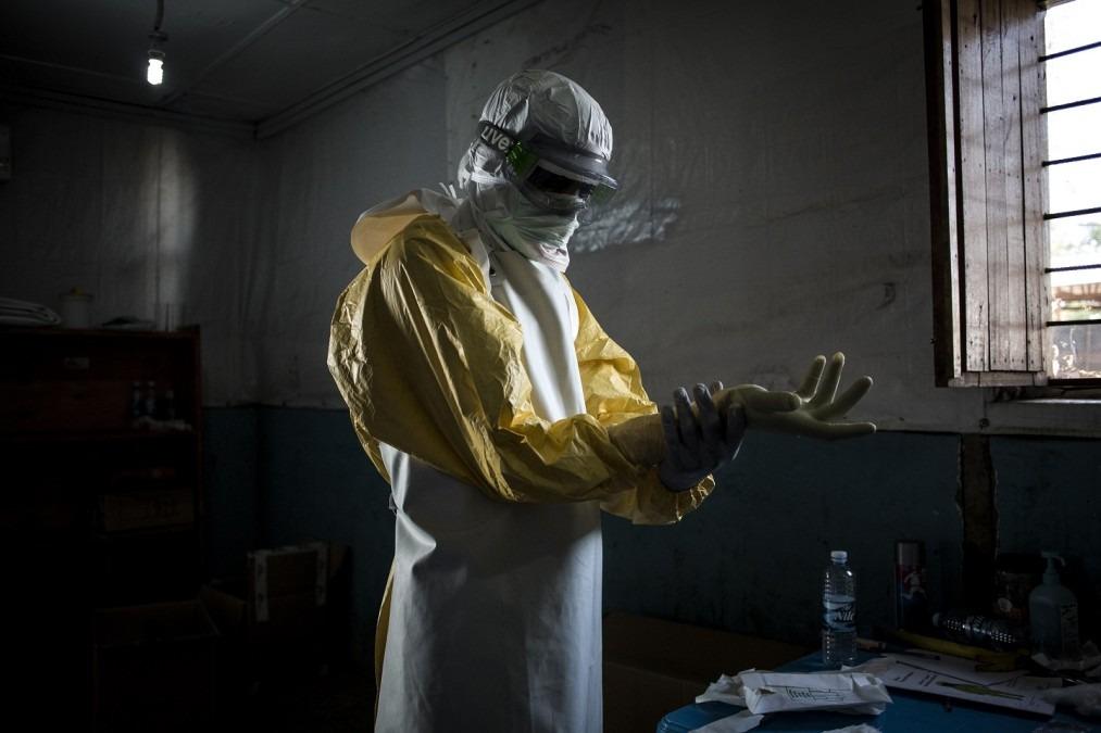 Un agent de santé en train de mettre son équipement de protection individuelle avant d'entrer dans la zone rouge d'un centre de traitement Ebola soutenu par MSF. Novembre 2018. RDC. © John Wessels