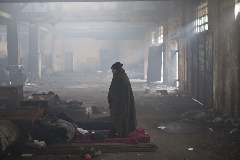 A man stands inside a disused railway warehouse used by refugees and migrants as shelter in Belgrade, Serbia, on 5 January 2017.   © Marko Drobnjakovic