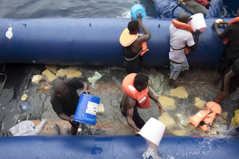 Un groupe de personnes tente de vider l'eau du bateau avec lequel ils voyageaient. © Albert Masias/MSF