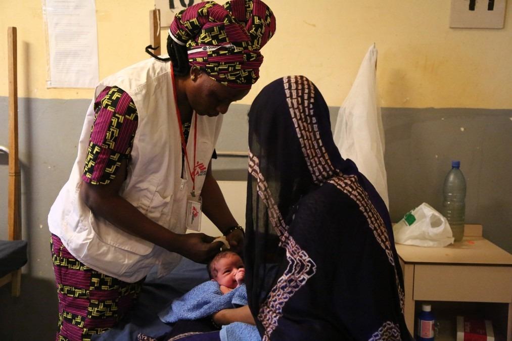 Aminata, sage-femme pour MSF à la maternité d'Ansongo, en train de faire une consultation pour un nouveau-né, Mali, décembre 2017. © Seydou Camara/MSF