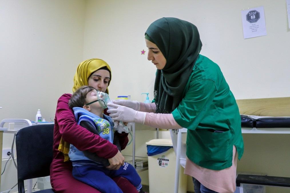 Die Krankenschwester Iman Hassam mit dem Baby Noor El Din and seiner Mutter Zeina in einem Raum der MSF Klinik in Jandoula. © Elisa Fourt/MSF