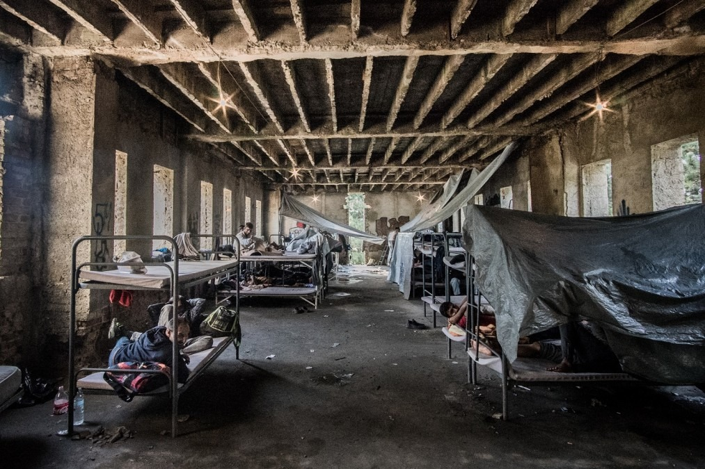One - and only one - room in this five-story abandoned concrete dormitory features bunk-bed cots for refugees and migrants to sleep. Flooding throughout the building is a frequent problem. Bihać, Bosnia, July 2018. © Kamila Stepien