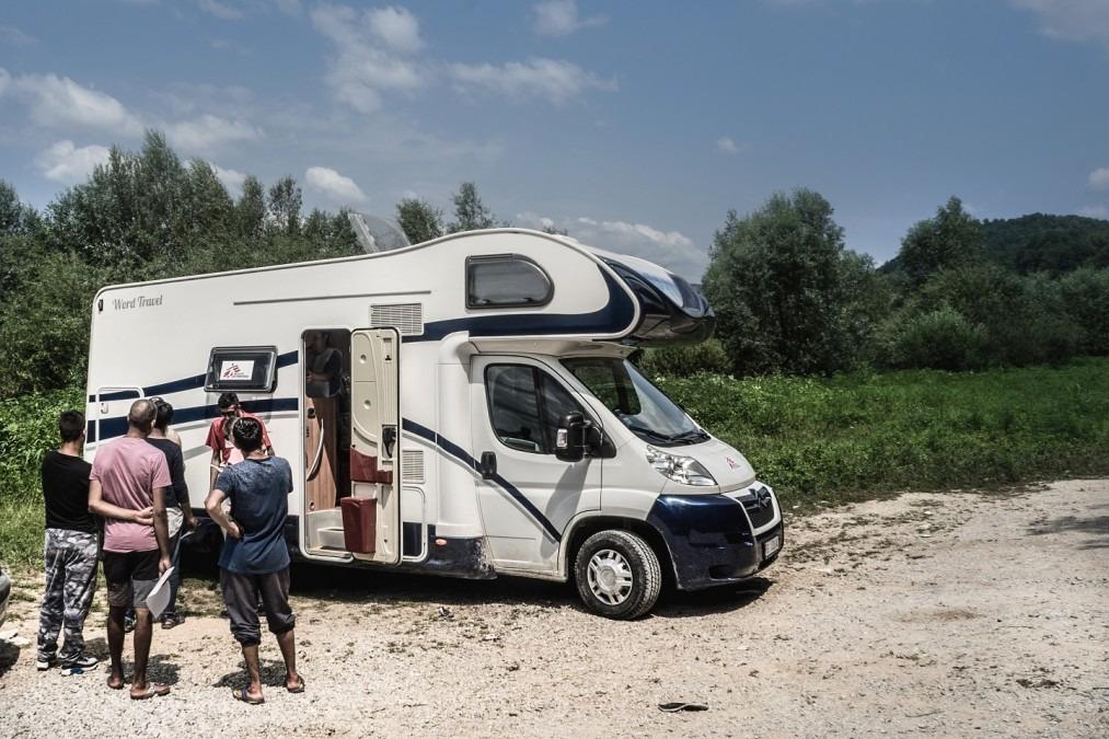 Patients wait outside MSF's mobile clinic in Velika Kladuša, Bosnia, near the Croatian border. July 2018. © Kamila Stepien