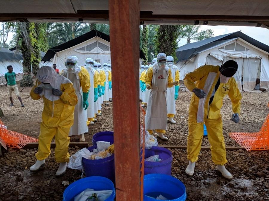 Une équipe retire son équipement de protection individuelle après avoir monté une tente dans la zone de haut risque dans le centre de traitement Ébola. Nord-Kivu, République démocratique du Congo, Août 2018. © Karin Huster/MSF