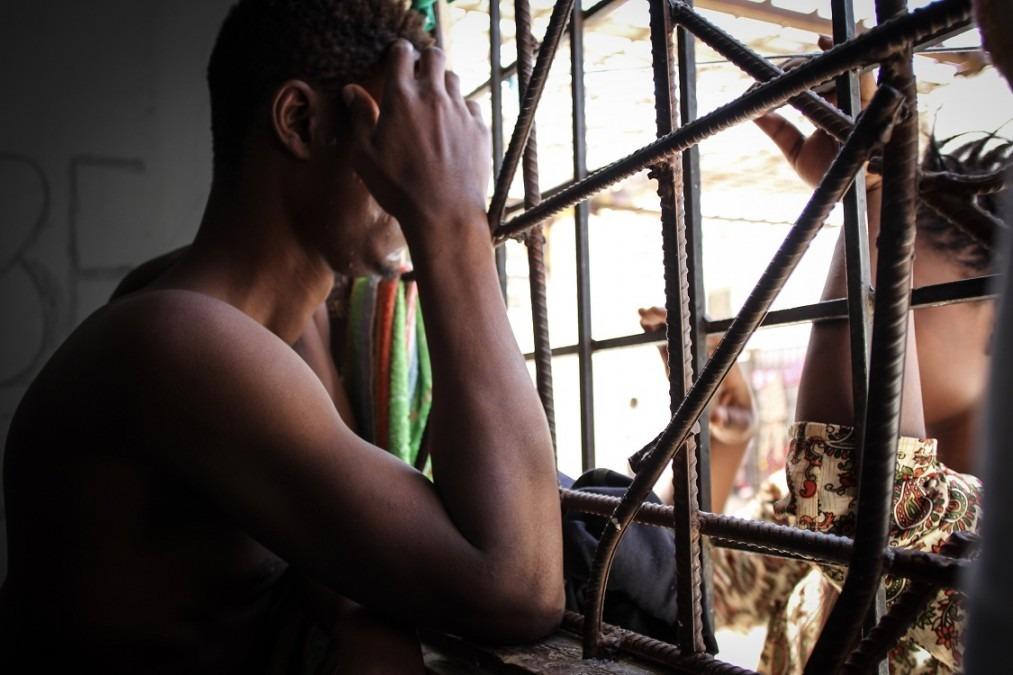 Un jeune couple est tenu à l'écart et tous les jours, quand les gardes le permettent, ils se retrouvent au travers de la fenêtre. Libye, septembre 2018. © Sara Creta/MSF