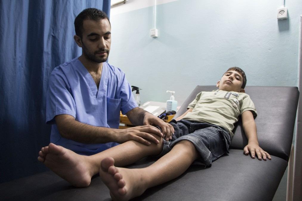 Fadi Jehad Alwadia, kinésithérapeute de MSF, avec Mohamed, 9 ans. Palestine. Septembre 2018. ©Alva Simpson White/MSF