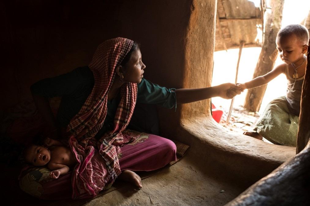 Zaida Begum, une réfugiée rohingya âgée de 20 ans, tient l'un de ses enfants dans son bras, Omma Habiba, né à 2 heures du matin le jour où cette photo a été prise. District de Cox's Bazar, Bangladesh. Août, 2018. © Robin Hammond/NOOR