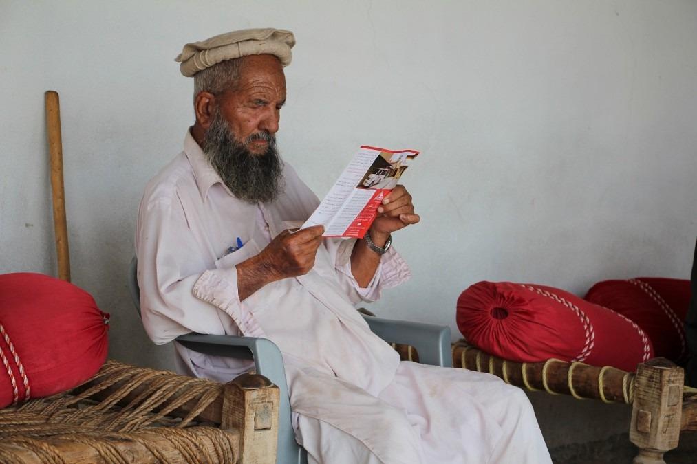 Un participant à l'une des sessions de sensibilisation sur la santé maternelle et infantile, délivrées par MSF dans les régions rurales, en train de lire la brochure MSF. Pakistan, octobre 2018. © Nasir Ghafoor/MSF