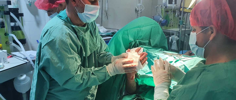 Salle d'opération de l'unité de traumatologie d'urgence de MSF à Kunduz, les équipes chirurgicales de MSF réalisent une opération sur un patient blessé par les combats à Kunduz. Août 2021.